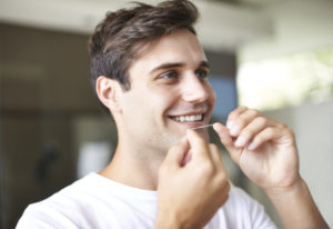 Closeup of a young man flossing